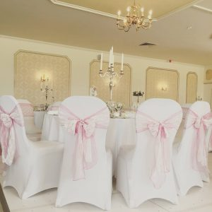 Chair covers with pale pink organza bows, lace overlay and pearl detail
